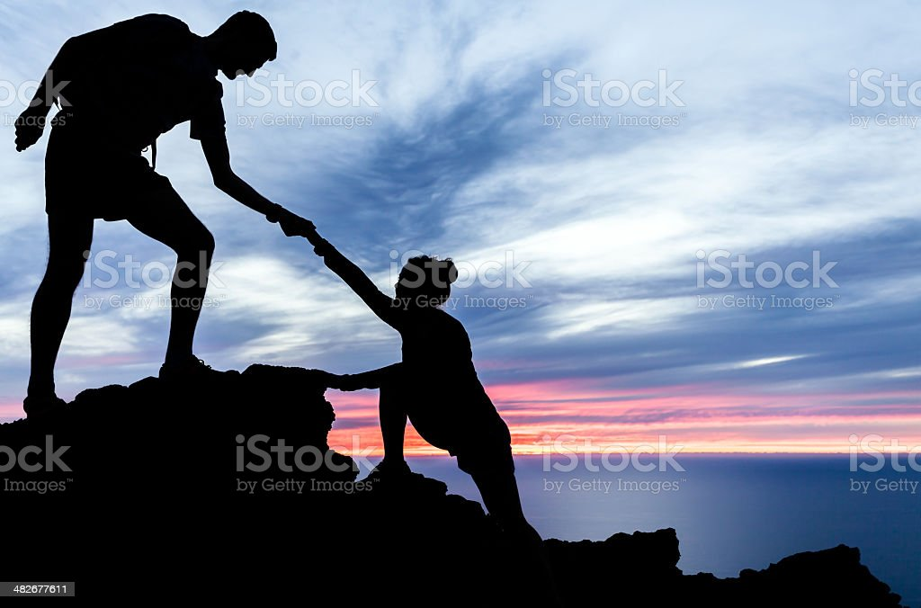Man and woman hiking silhouette in mountains stock photo