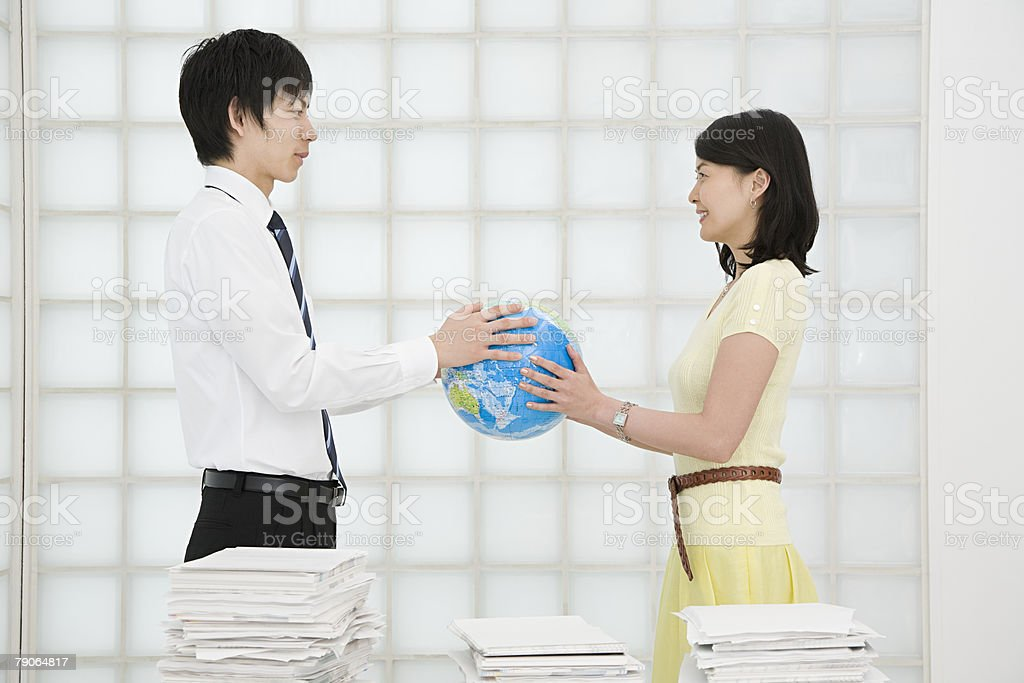 A man and woman holding a globe stock photo