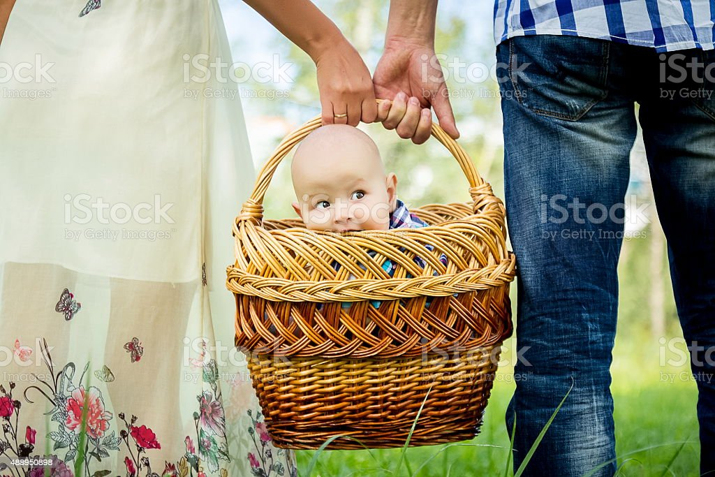 Man and woman holding basket with little boy stock photo