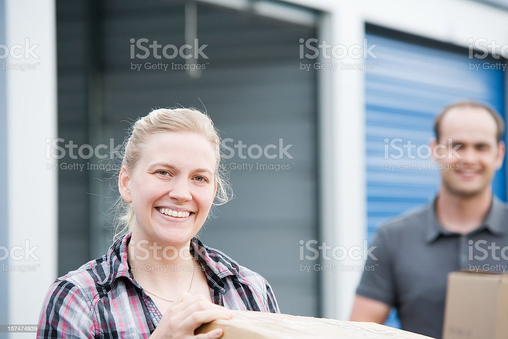 Man and Woman Holding Boxes at Self Storage Unit stock photo
