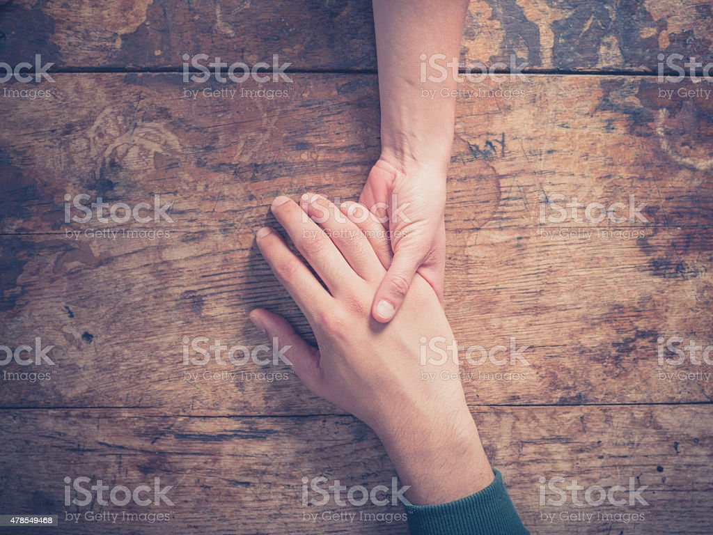 Man and woman holding hands at a table stock photo