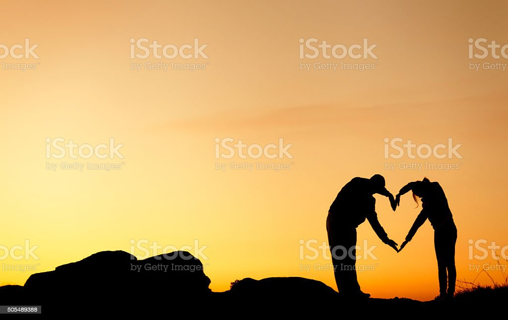 Man and woman holding hands in heart shape at sunset stock photo