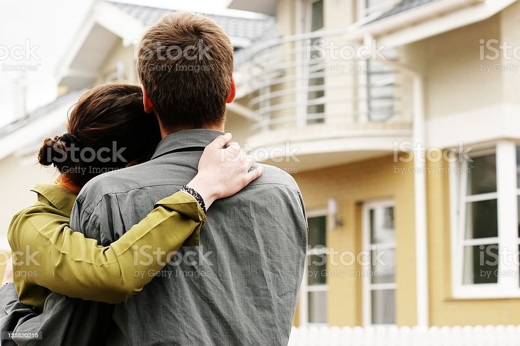 Man and woman hugging in front of a house royalty-free stock photo
