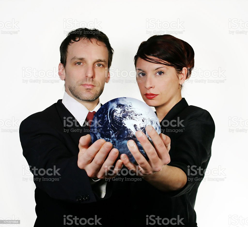 Man and woman in business attire holding the world. royalty-free stock photo