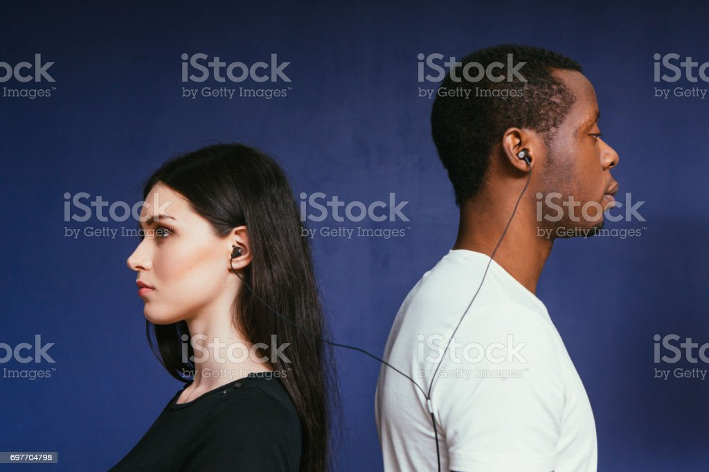Man and woman in earphones. International couple stock photo