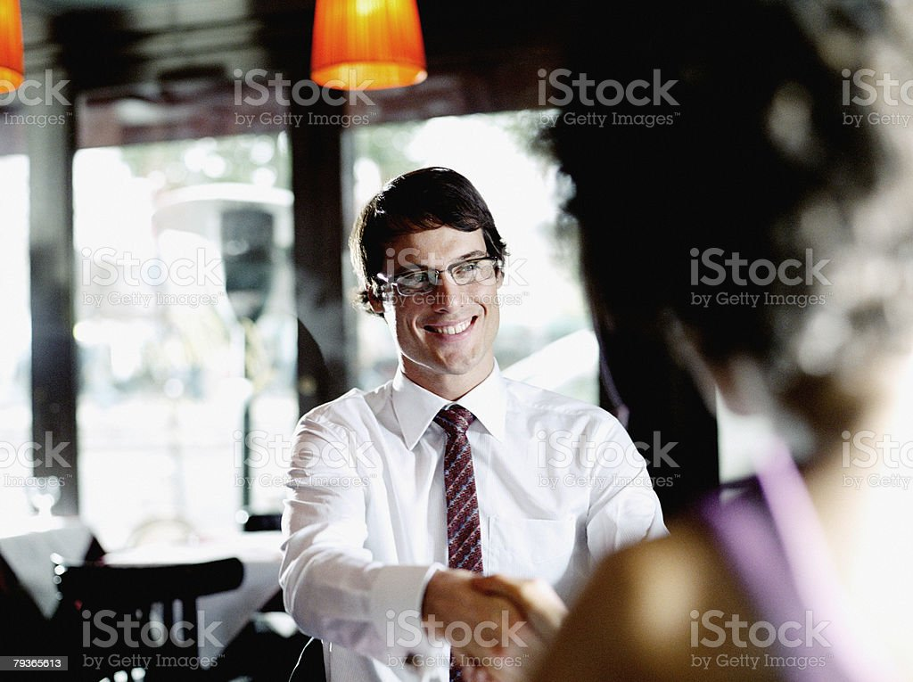 Man and woman in restaurant shaking hands royalty-free stock photo