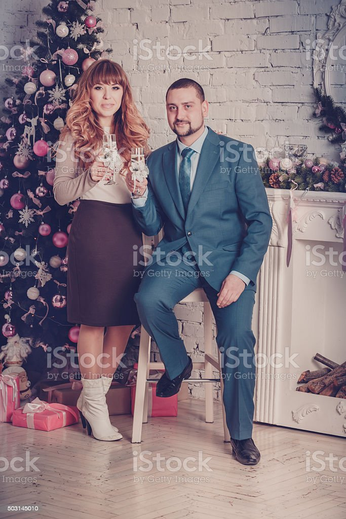 Man and woman in room with Christmas tree and fireplace stock photo