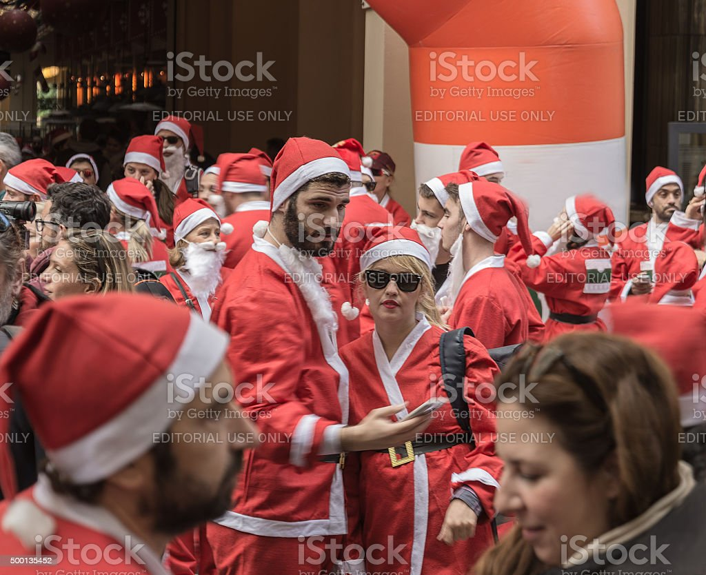 man and woman in the foreground dressed as Santa Claus stock photo