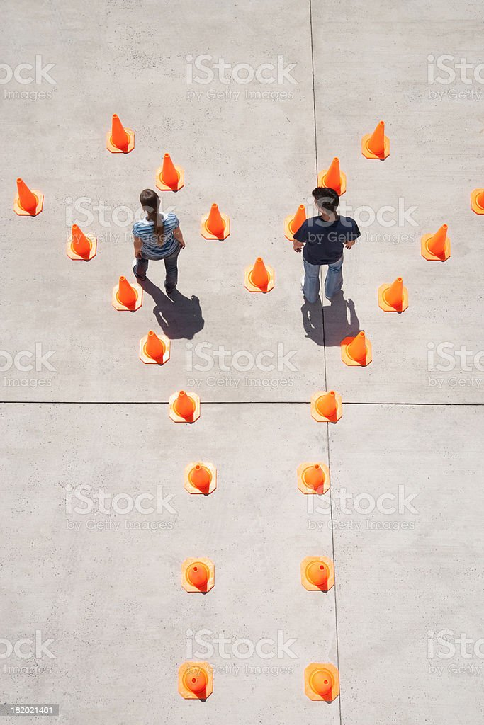 Man and woman in traffic cones moving apart stock photo