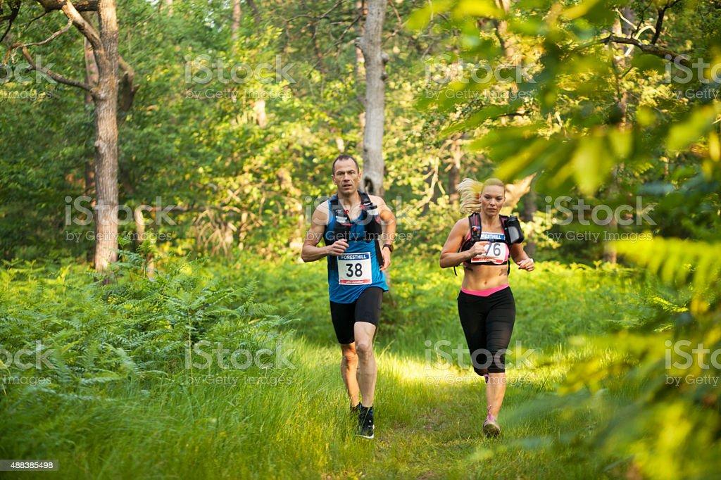 Man and woman in ultramarathon race stock photo