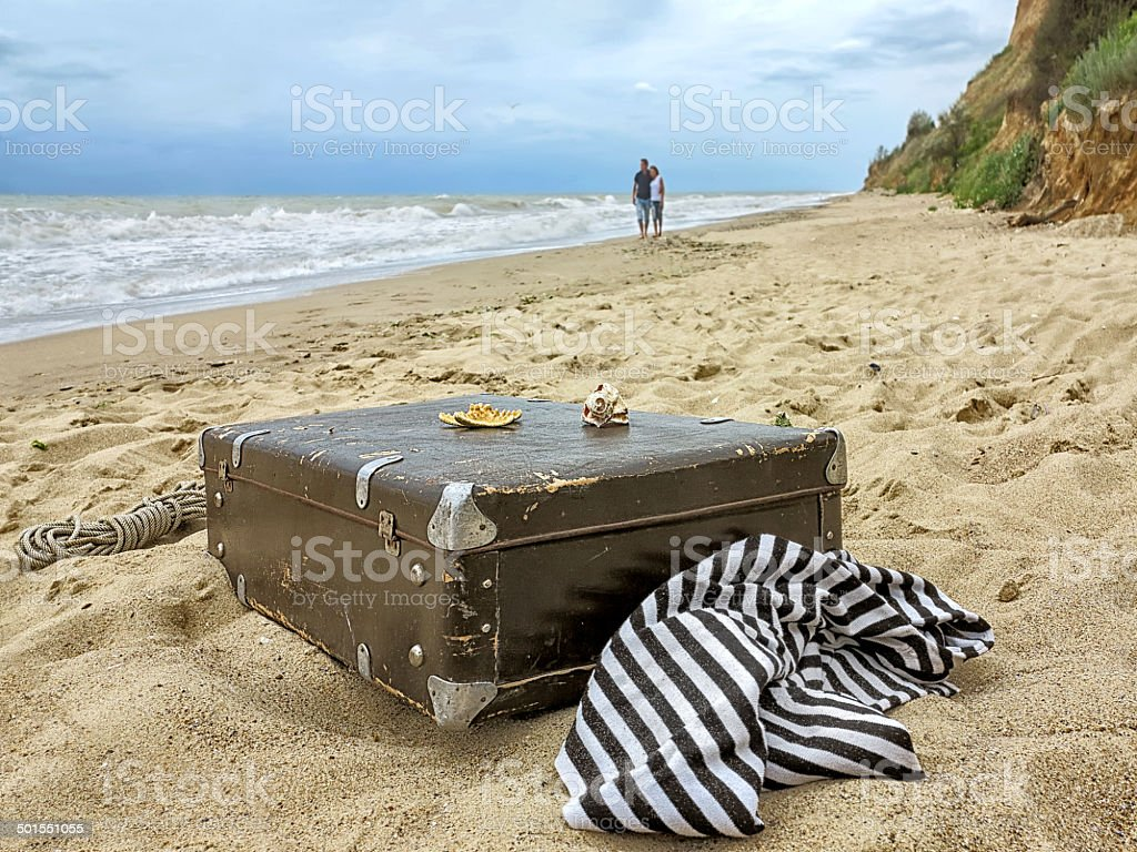 man and woman in walk on the sand along the sea stock photo