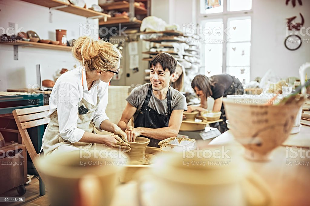 Man and woman in workshop working on pottery wheel stock photo