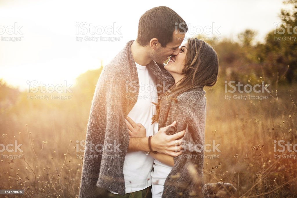 Man and woman kissing outdoors at sunset stock photo