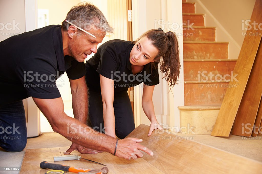 Man and woman laying wood panel flooring in a house stock photo