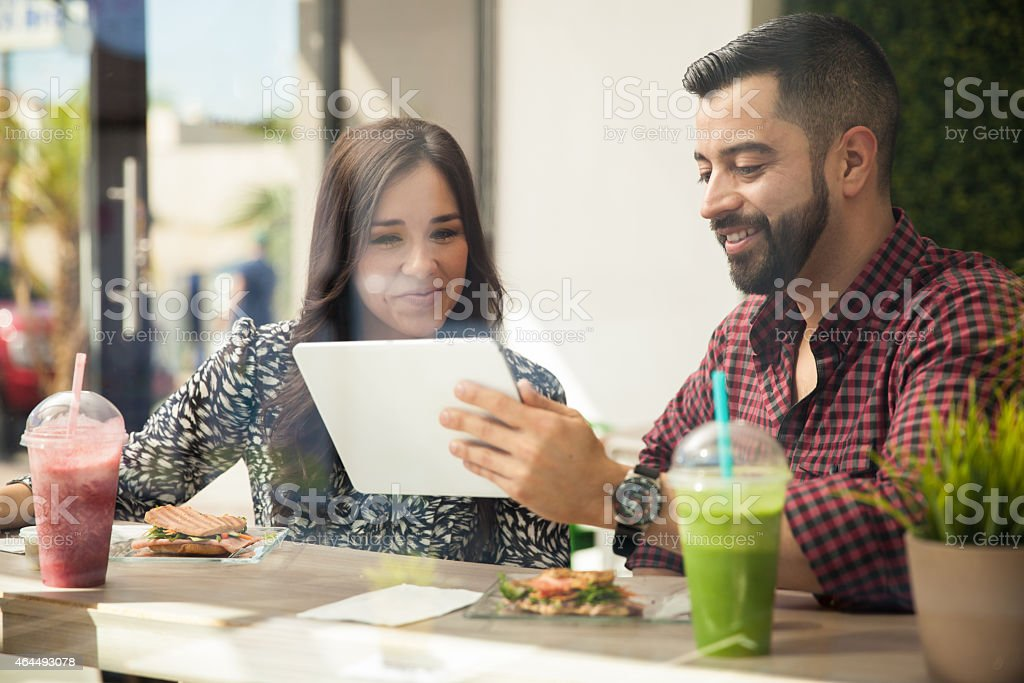 Man and woman looking at a tablet at lunch stock photo