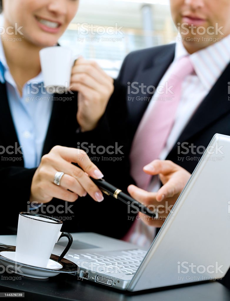 Man and woman looking at computer with a cup of coffee  stock photo
