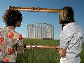 man and woman looking at house through frame