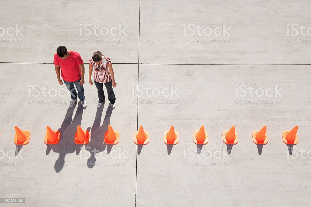 Man and woman looking at row of traffic cones stock photo