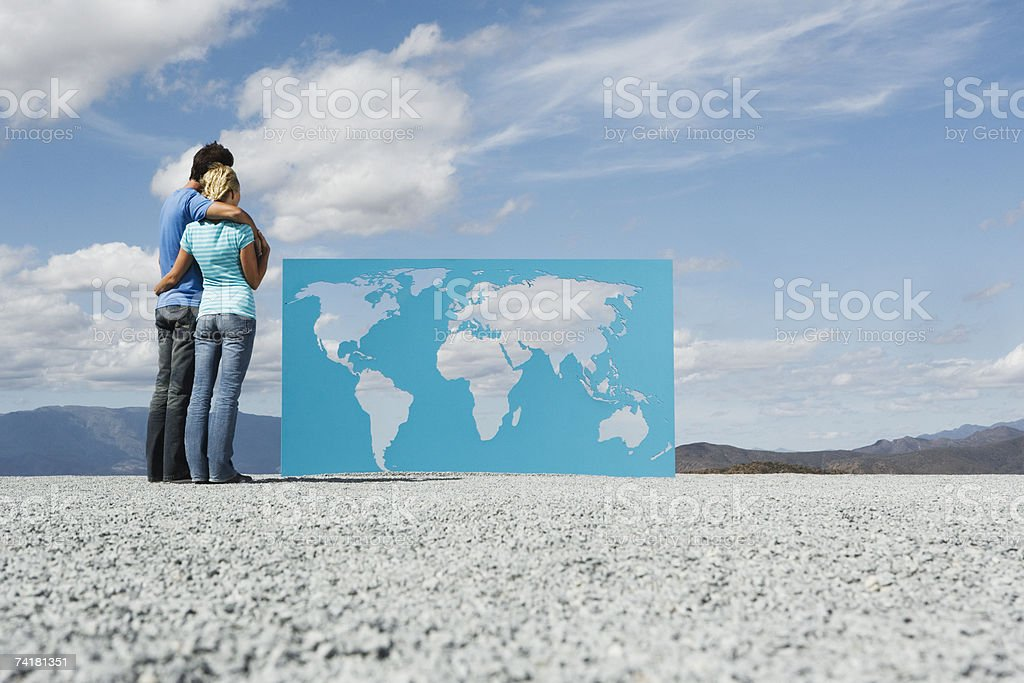 Man and woman looking at world map outdoors stock photo