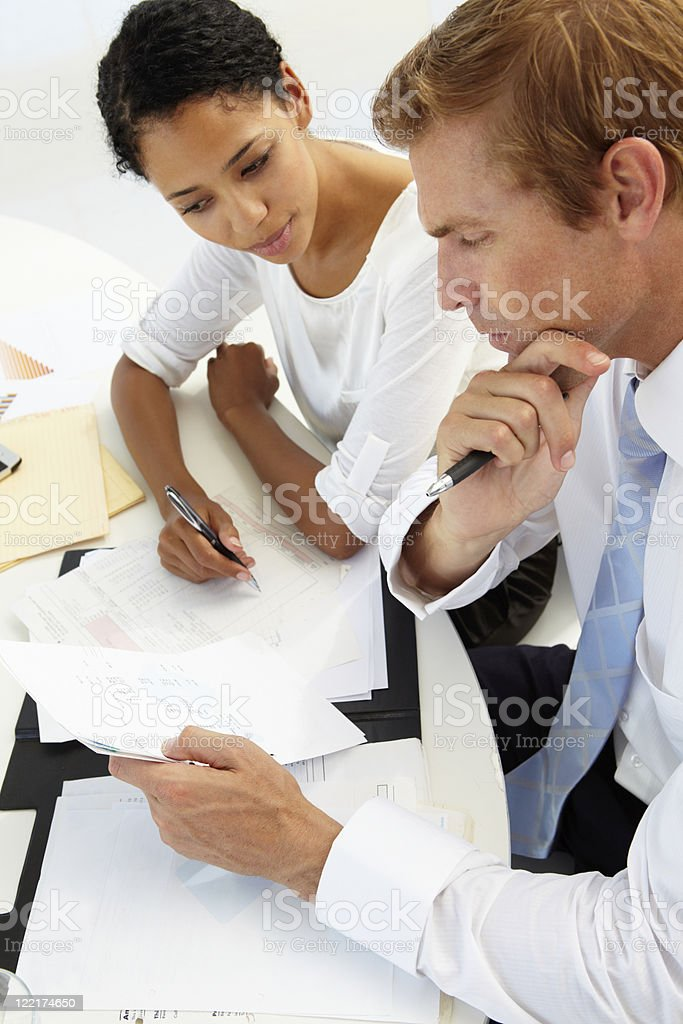 Man and woman looking over papers royalty-free stock photo