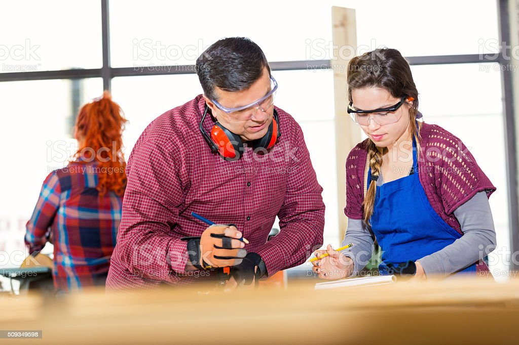 Man and woman measure board in woodworking shop stock photo