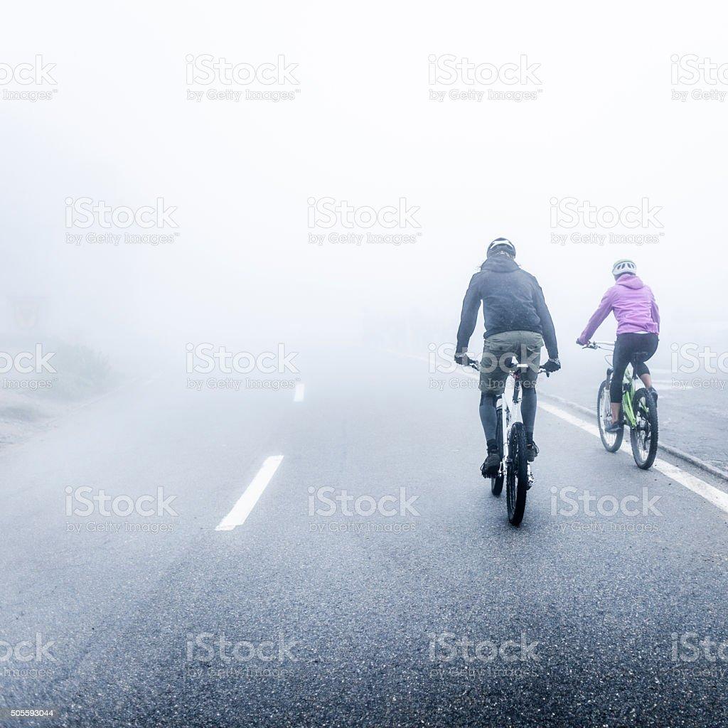 Man and Woman Mountain Biking in Fog stock photo