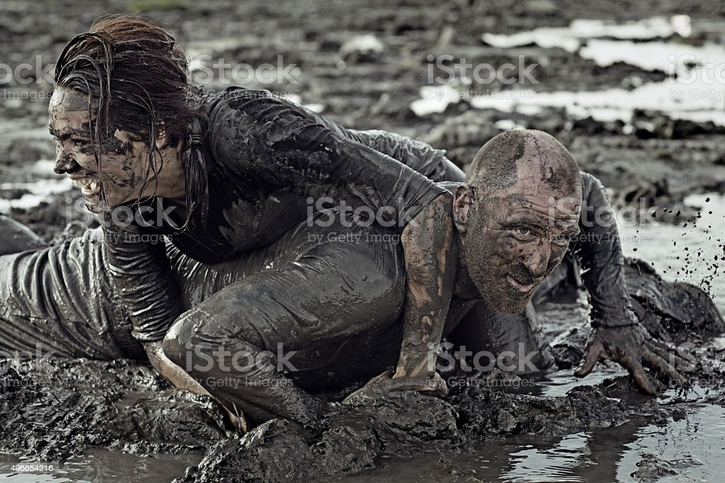 man and woman mud wrestling stock photo