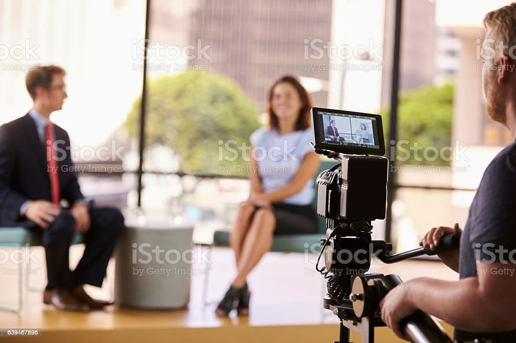 Man and woman on set for a TV interview, focus on stock photo