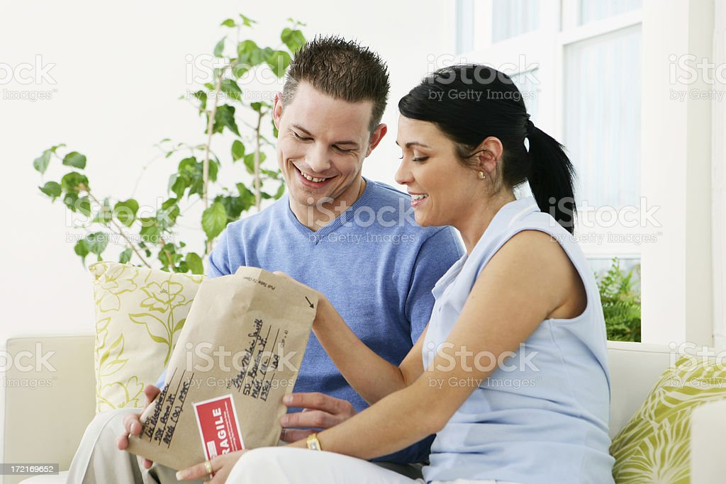 Man and woman opening a package royalty-free stock photo