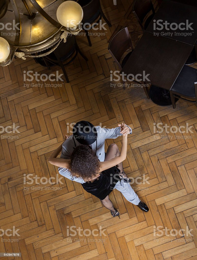 Man And Woman Performing Tango On Wooden Floor stock photo