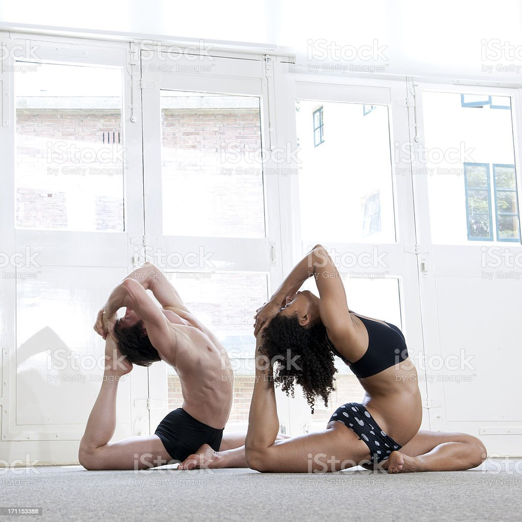 man and woman performing yoga pigeon pose royalty-free stock photo