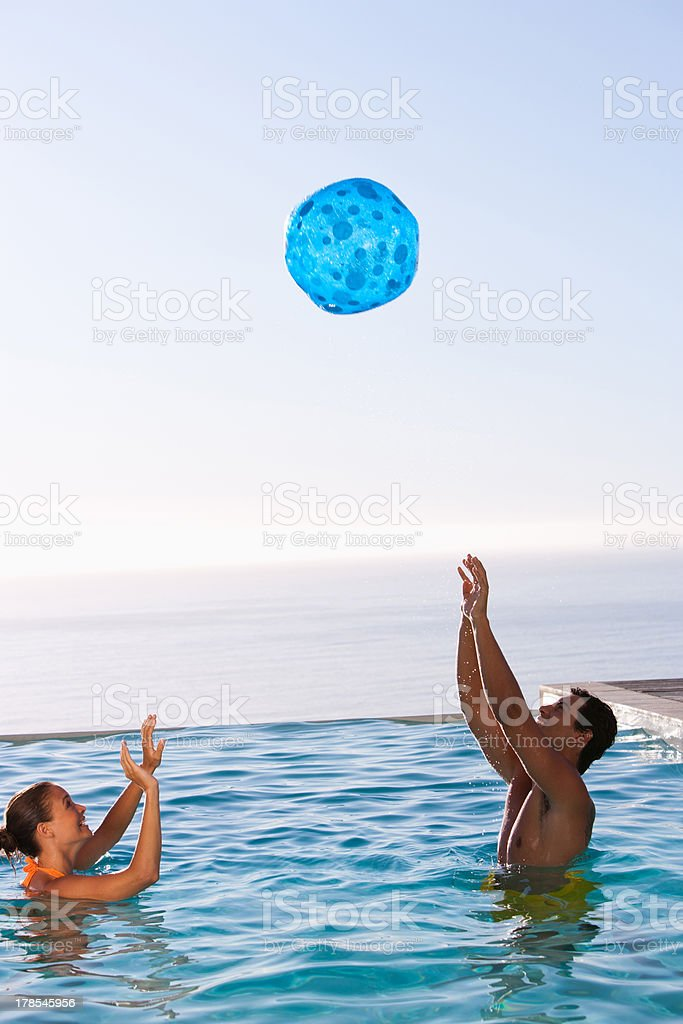 Man and woman playing with ball in swimming pool royalty-free stock photo