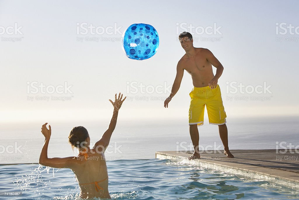 Man and woman playing with beach ball in infinity pool royalty-free stock photo