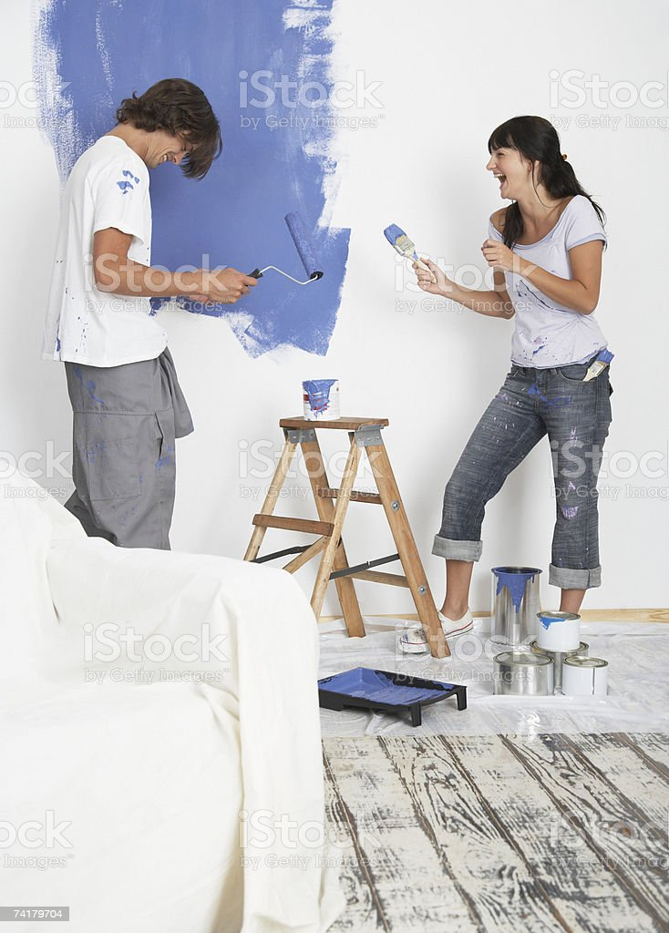 Man and woman playing with paint and laughing stock photo