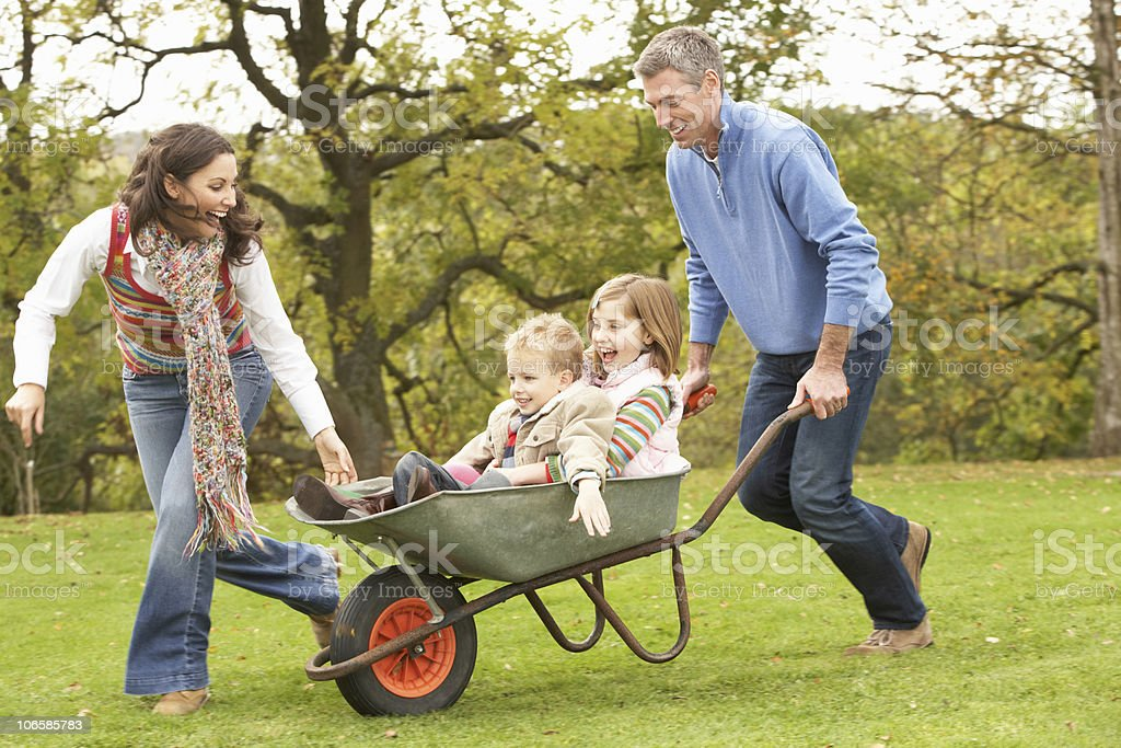 Man and woman playing with two small children in wheelbarrow stock photo