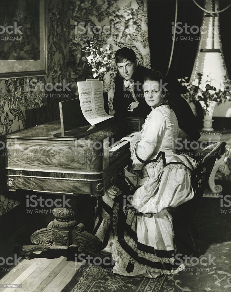 Man and woman posing at spinet, (B&W), portrait stock photo