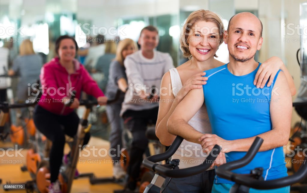 man and woman posing in a gym and smiling stock photo