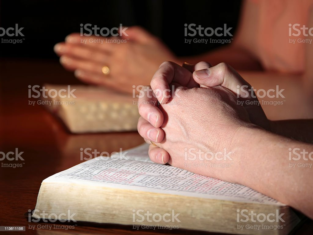 Man and Woman Praying with Holy Bibles stock photo