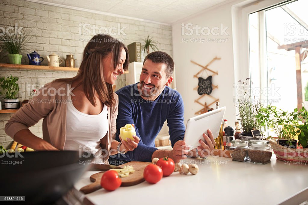 Man and woman preparing dinner using tablet stock photo
