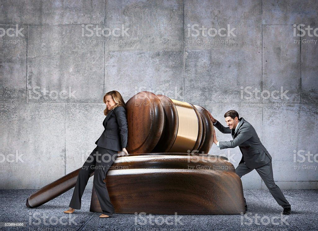Man And Woman Pushing In Opposite Directions Against Large Gavel stock photo