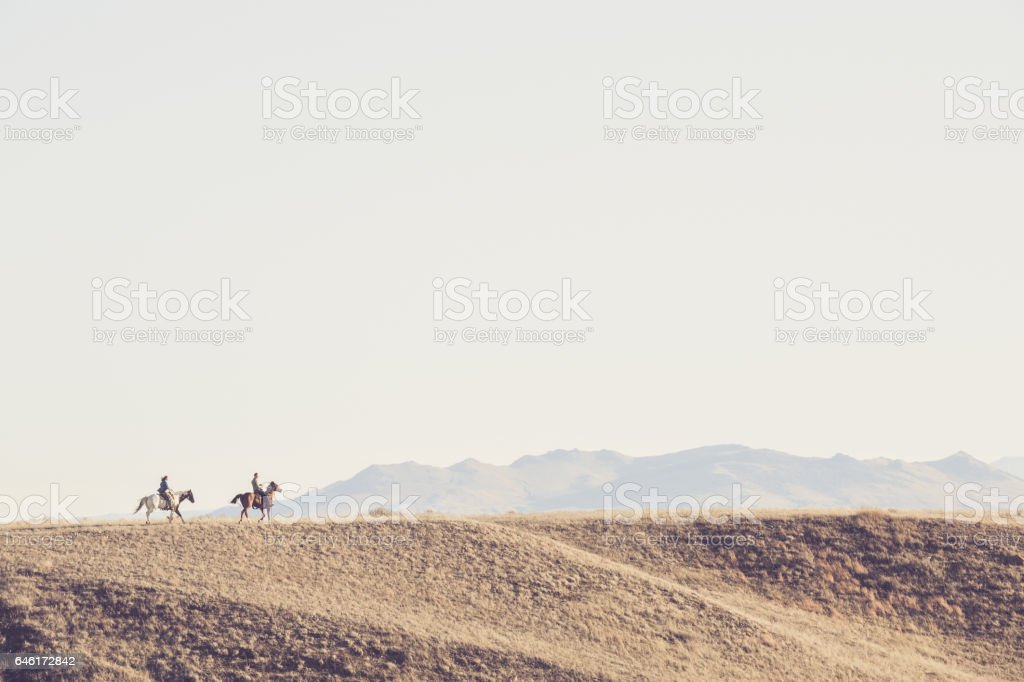 Man And Woman Riding Horseback Across A Montana Landscape stock photo