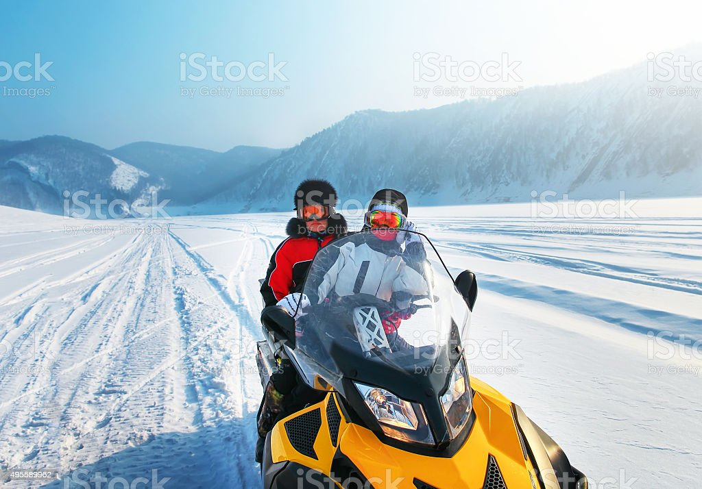 Man and woman riding on snowmobile stock photo