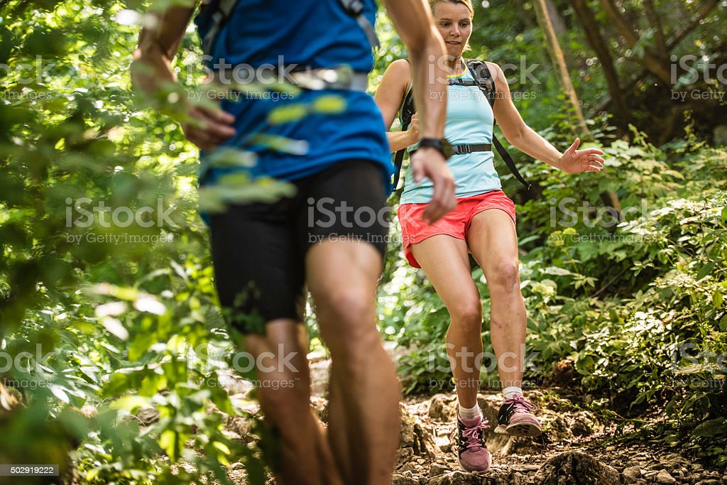 Man and woman running down a rocky woodland path stock photo