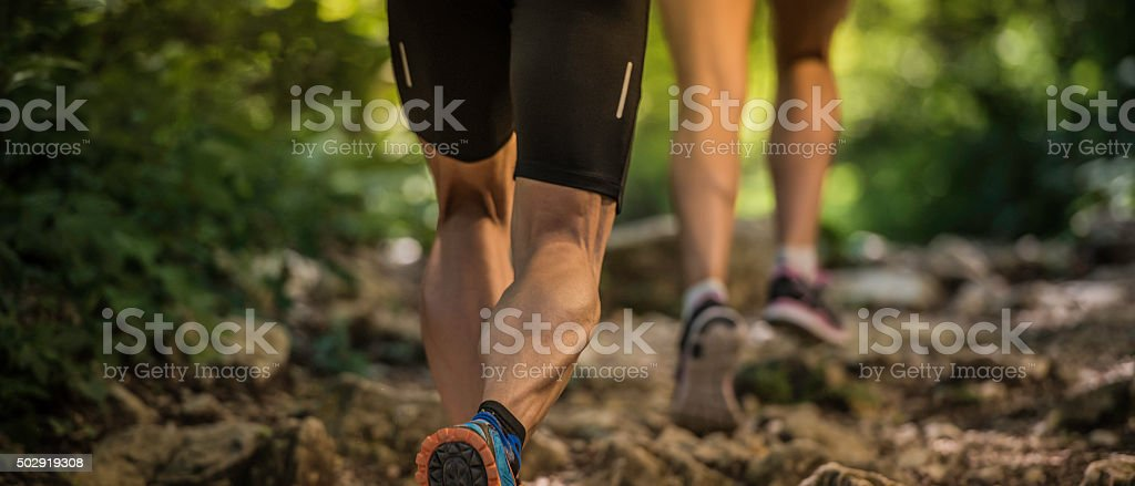 Man and woman running on a rocky forest path stock photo