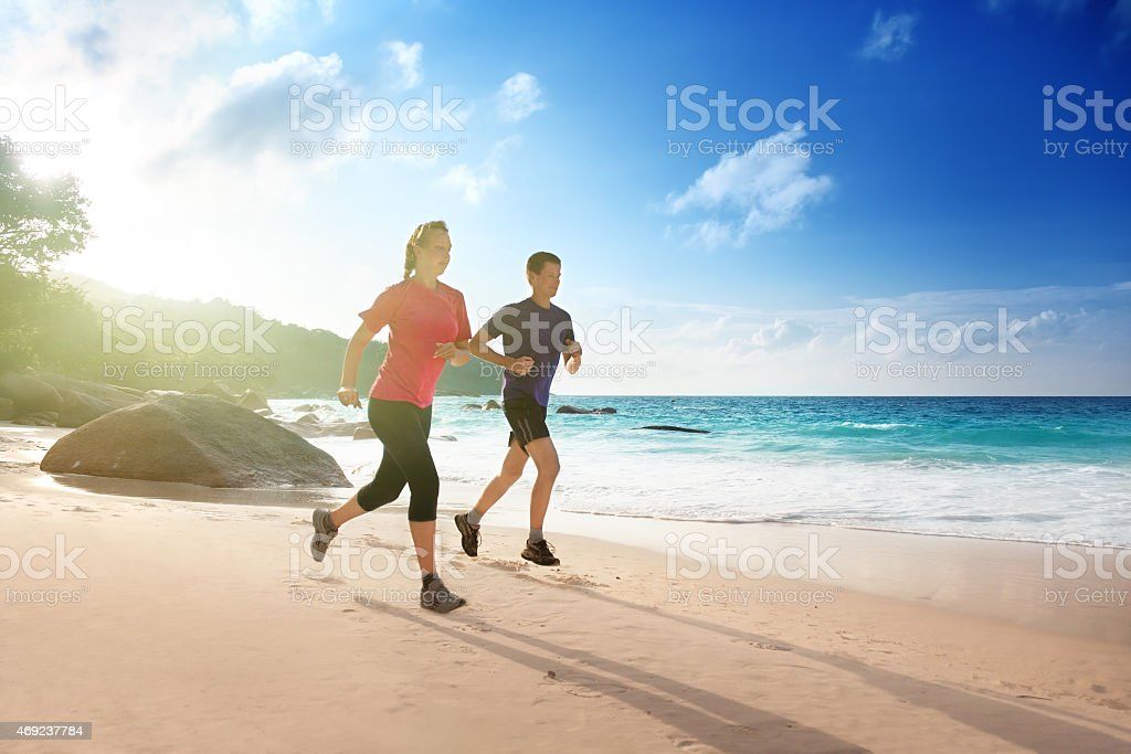 Man and woman running on tropical beach at sunset stock photo