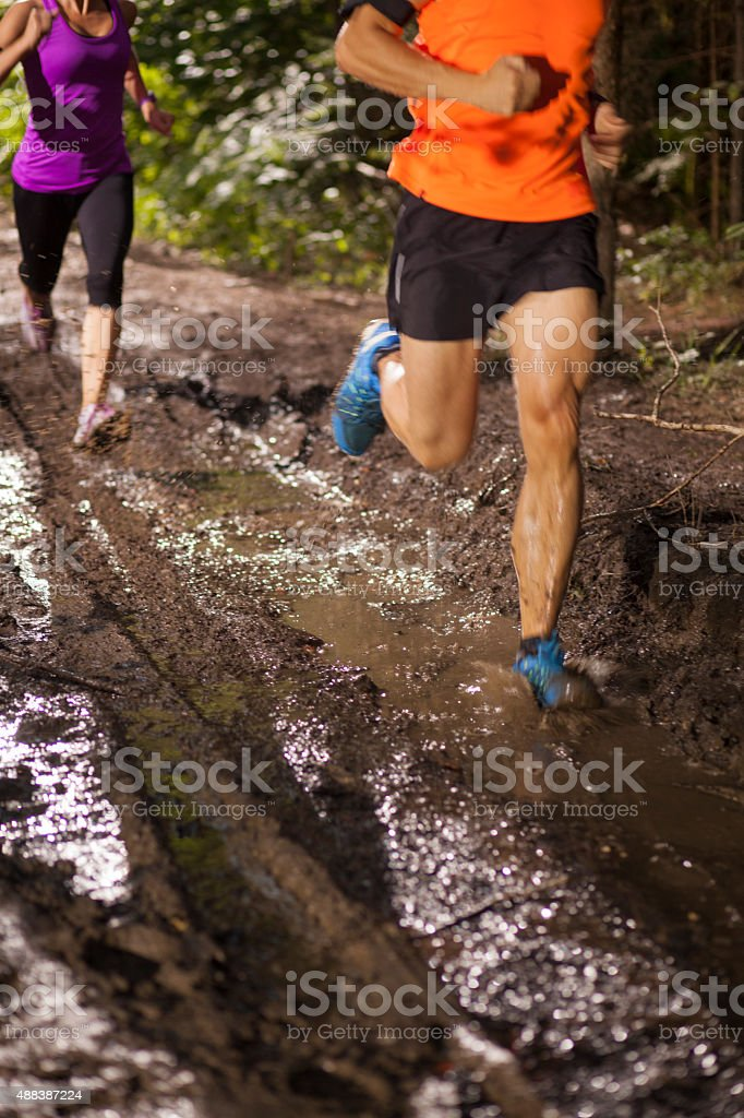 Man and woman running through dirt track in ultramarathon race stock photo