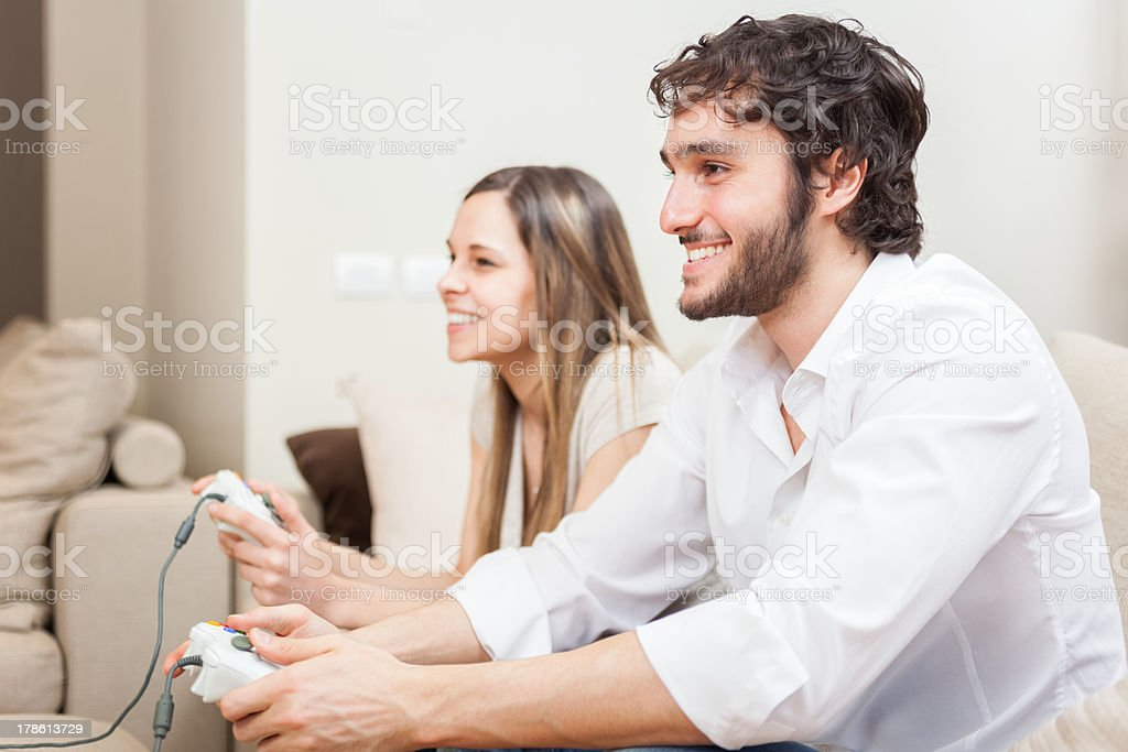 Man and woman sat with game controllers in their hands royalty-free stock photo