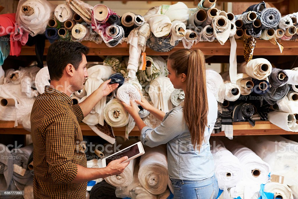 Man and woman selecting fabric from storage shelves stock photo