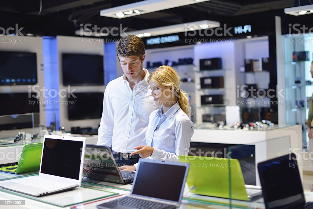 Man and woman shopping for laptop in electronics store stock photo