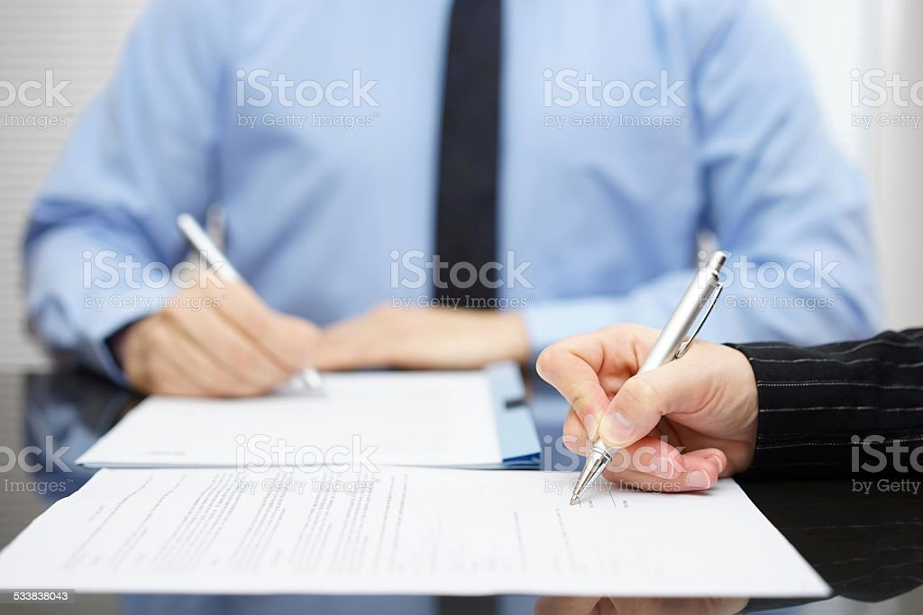 Man and woman   signing a business contract after the conclusion stock photo